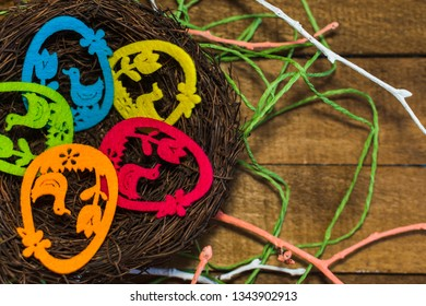 decorative eggs in nest on wooden background. happy Easter card.
