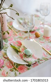 Decorative festive table setting with floral tablecloth, egg, dish and golden cutlery, glass for wine, willow branch. Happy easter holidsy concept.