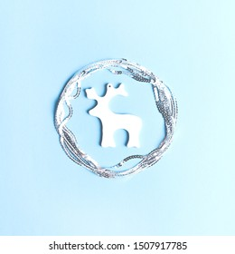 Decorative figurine of a deer in a circle of sequins on a blue background.