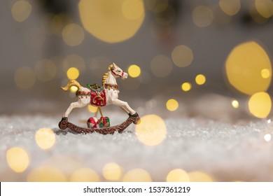 Decorative figurines of a Christmas theme. Figurine of a rocking horse. Decoration for a Christmas tree. Festive decor, warm bokeh lights