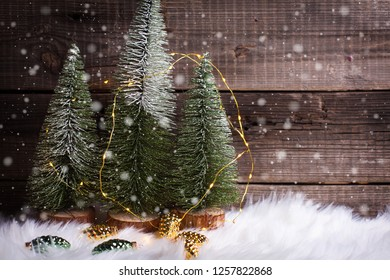 Decorative fir trees, golden and green decorative pine cones and fairy lights on white fur background against vintage wooden wall. Selective focus. Place for text.