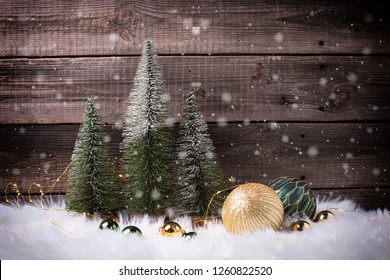 Decorative fir trees,  golden and green balls and fairy lights on white fur background against vintage wooden wall. Selective focus. Place for text.