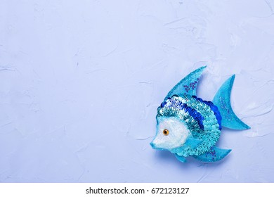 Decorative fish on  blue textured  background. Selective focus. Place for text.