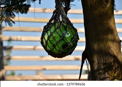 Decorative fishing net floater hang on the tree in the backyard