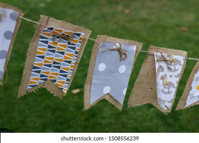 Decorative flags of burlap and textile for holiday decoration hang on a rope in a letos garden