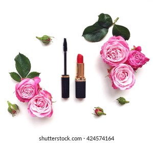 Decorative flat lay composition with cosmetics and flowers. Top view on white background
