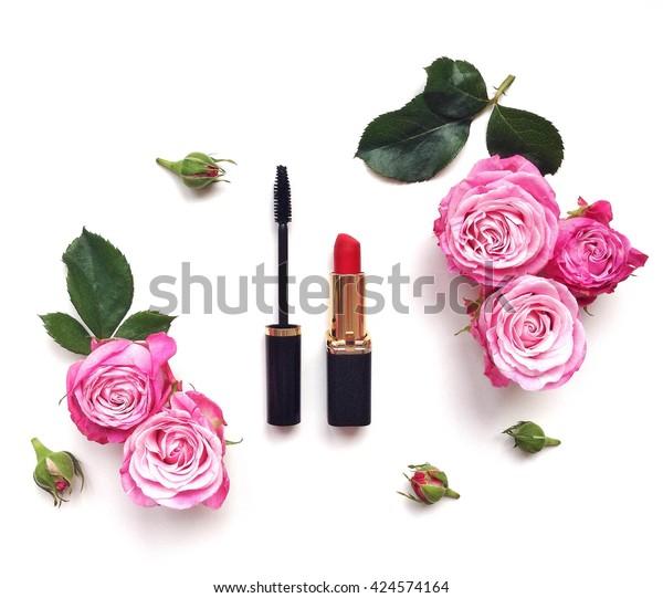 化粧品と花を含む装飾的なフラットレイ組成物。白い背景に上面図
