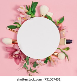 Decorative flat lay composition with makeup products, cosmetics and flowers. Flat lay, top view on pink background