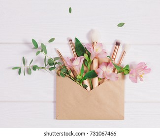 Decorative flat lay composition with makeup products, kraft envelope and flowers. Flat lay, top view on white background