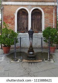Decorative fountain with a bowl of water for dogs, flanked by two flower pots, in front of a house in Murano, Venice, Italy