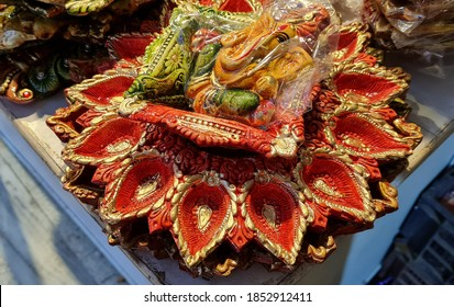Decorative fouteen lamps or diyas clinging to a stand in a circular shape with lord ganesha statue on the top are on sale for diwali and deepavali.