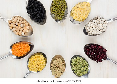 Decorative frame of assortment different beans in  spoons with copy space on white wood background. Top view, closeup.