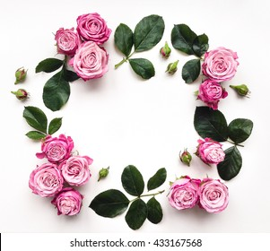 Decorative frame with pink bright roses and leaves on white background. Flat lay