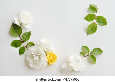 Decorative frame with white and yellow bright roses and leaves on white background. Flat lay flowers. Frame wreath. Top view