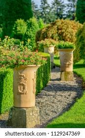 Decorative garden plant pots in a formal garden in autumn.