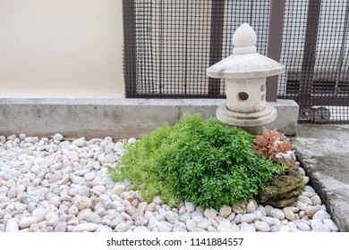 Decorative Garden Stone Lantern With Green Bush On White Rock