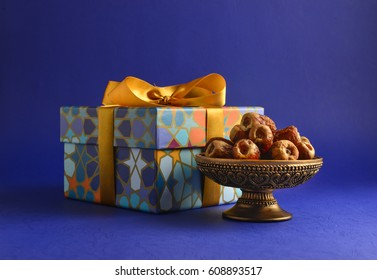Decorative gift box with golden ribbon and dates. Islamic festive gift and dates. Stock photo.