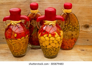 Decorative glass amphora bottle with canned vegetables, garlic, lemon, beans, peppers, carrots, tomatoes, olives,  with red wax, natural twine on wooden background