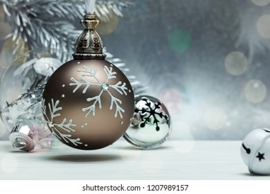 decorative glass balls and jingle bells for christmas tree on grey background with blurred fir tree branch