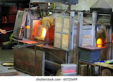 Decorative glass being manufactured at Murano, Venice, Italy. A glassmaker is removing a blob of molten glass on a the end blowpipe from the furnace