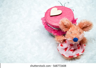 Decorative glass jar with a heart from a tree and a toy mouse
