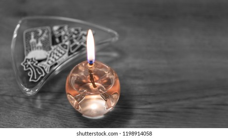 Decorative glass lamp with aromatic oil. Ornate Xmas gingerbreads. Orange burning candle on black and white blurry wood background with triangle bowl of traditional sweets. Melancholy Christmas scene.