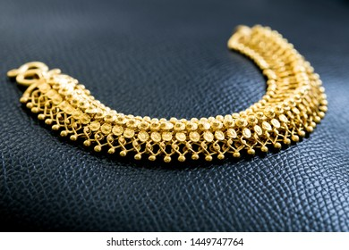 A decorative gold charm bracelet on black leather background. an article of jewellery that is worn around the wrist. Expensive luxury gold bracelet for anniversary gift with copyspace,selective focus.