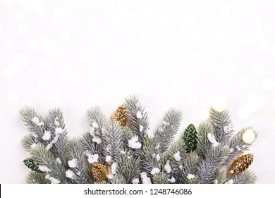 Decorative golden and green  pine cones and branches fur tree on  white textured  background. Christmas , new year, winter holidays composition. Selective focus. Place for text. View from above.