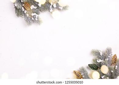 Decorative golden and green  pine cones and branches fur tree with bokeh lights on  white textured  background. Christmas , new year, winter holidays. Selective focus. Place for text. View from above.