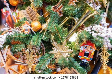 Decorative green Christmas tree decorated with toys Nutcracker, trumpet, Golden snowflake and gold ornaments