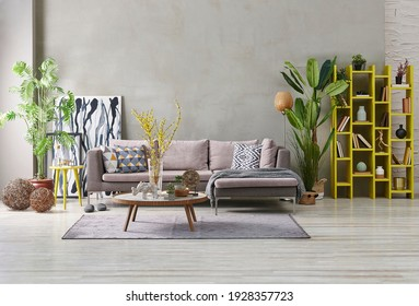 Decorative grey sofa and wall background stone style. yellow niche, home accessory, yellow bookshelf concept, poster frame orange lamp decor.