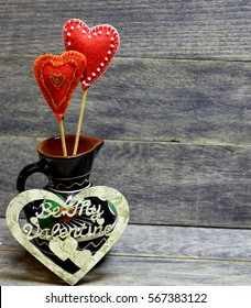 Decorative hand made hearts in small folk style vase on wooden background. Crafts from felt decorated with beads and decoupage. Beautiful card background for St. Valentine`s day. Copyspace.