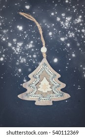 Decorative handmade christmas tree on black wooden background with snow