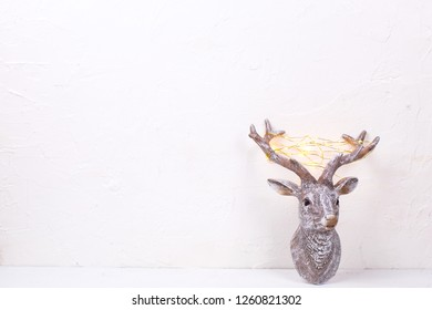 Decorative head of New Year reindeer with fairy light on its antlers on white textured background. Selective focus. Place for text.