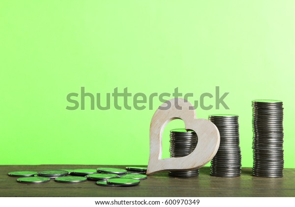 Decorative heart and coins on a wooden table on a green background