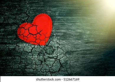 Decorative heart on dark wooden background with bright white light from the window. The concept of fading love. The end of life. On the verge of death. The aging of the human body. Heart disease.
