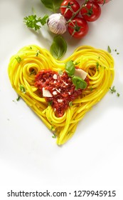 Decorative heart shaped spaghetti Bolognaise topped with tomato sauce, parmesan cheese and basil with fresh ingredients above over a white background with copy space