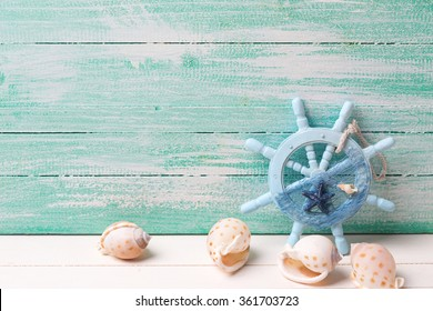 Decorative helm and marine items on turquoise wooden background.  Selective focus. Place for text.