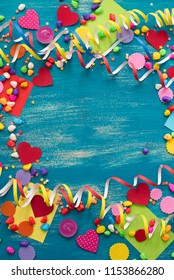 Decorative holiday background with streamers confetti candy hearts decor. Blue shabby wooden top view background flat lay