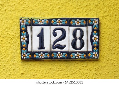 Decorative house number sign on yellow wall facade