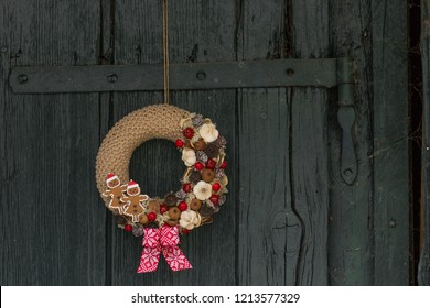 Decorative knitted christmas door wreath on wooden background