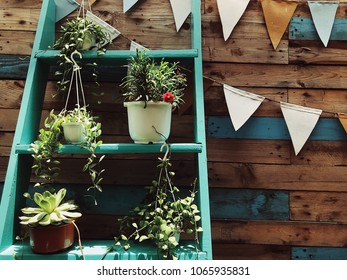 Decorative ladder shelf with pots of flowers and textile party flags in wooden wall background