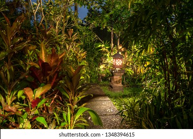 Decorative lamp on the stone pillar next to the path in the tropical garden at night . Ubud, island Bali, Indonesia . Nature concept