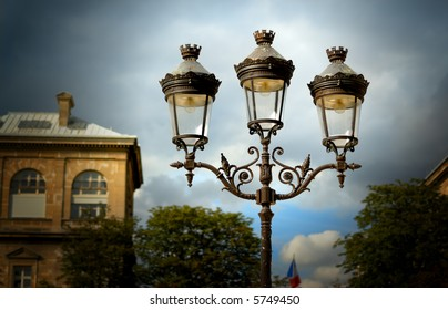 Decorative lamps against a cloudy sky outside of Notre Dame Cathedral in Paris, France, with building in the background.