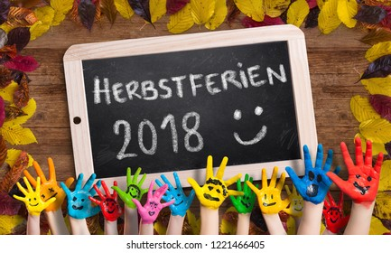 """decorative leaves on wooden background with a blackboard and the German message for """"fall break 2018"""""""