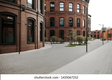 Decorative lighting pole in cityscape. Modern loft building from red brick in downtown area. Manufacture Arma in Moscow. Industrial design in city architecture. Business concept.