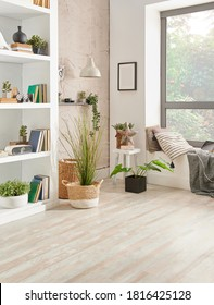 Decorative living room corner style with bookshelf vase of plant and blue armchair.