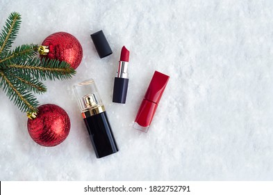decorative luxury cosmetics, red lipstick, nail polish, perfume under spruce branch with balls in the snow. gifts for women, girl for new year. Christmas sale. copy space, place for text. top view