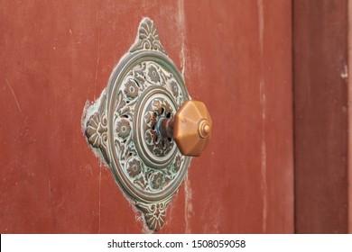 Decorative Maltese door knob on brown doors