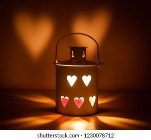 Decorative metal lantern with a heart cutout lit by a glowing candle. Heart-shaped shadows on the wall. Ideal for Christmas or Valentine's Day